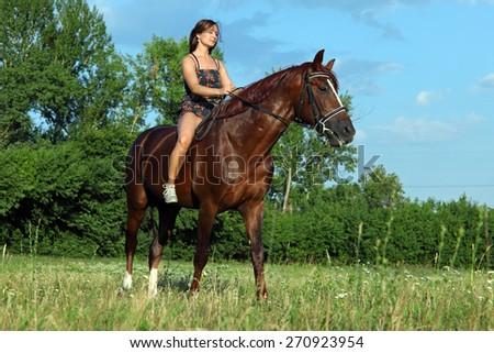 Romantic female model riding horseback - stock photo