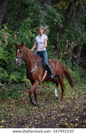 Romantic female rides purebred horse outdoors