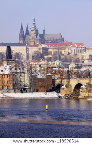 Romantic frozen snowy Prague gothic Castle with the Charles Bridge in the sunny Day,  Czech Republic