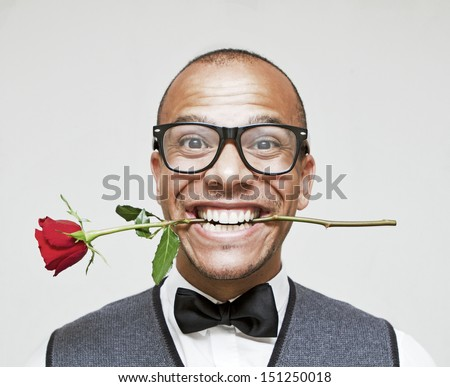 Romantic Geek in Love, holding a rose between his teeth excitedly - stock photo