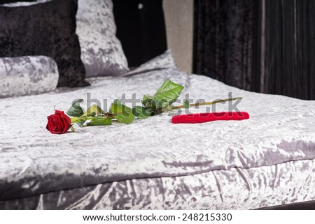 Romantic gift and single long stemmed red rose in a bedroom symbolising love for celebrating an anniversary or Valentines Day with a loved one - stock photo