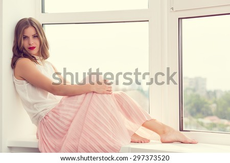 Romantic girl in long gown sitting by the window - stock photo