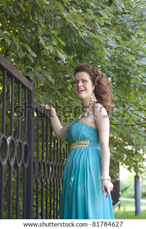 Romantic girl in the beautiful dress near the fence - stock photo