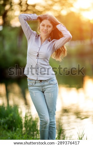Romantic girl outdoors enjoying nature Beautiful Model in Casual jeans in sun light Long healthy Hair  Backlit Warm Color Tones Beauty Sunshine woman Smiling Sunny Summer Day Autumn Summertime Glow