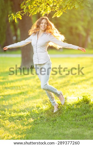 Romantic girl outdoors enjoying nature Beautiful Model in Casual jeans in sun light Long healthy Hair Blowing in Wind Backlit Warm Color Tones Sunshine woman  Sunny Summer Day Autumn Summertime Glow - stock photo