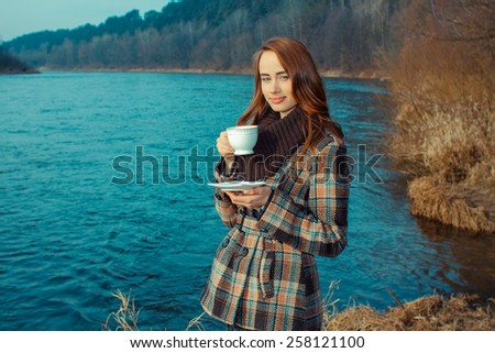 Romantic girl with cup outdoors. Hipster girl drinking tea in the spring in a landscape - stock photo