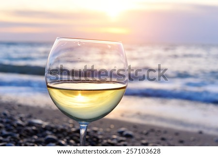 Romantic glass of wine sitting on the beach at colorful sunset Glasses of white wine against sunset, white wine on the sky background with clouds - stock photo
