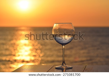 Romantic glass of wine sitting on the beach at colorful sunset Glasses of white wine against sunset, white wine on the sky  - stock photo