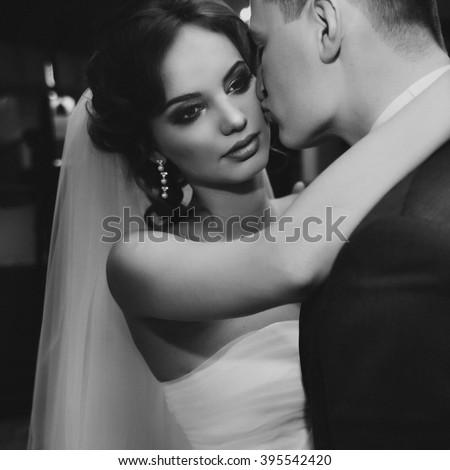 Romantic groom kissing beautiful bride on cheek closeup b&w - stock photo