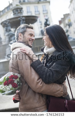 romantic guy holding red roses behind his back for his girlfriend