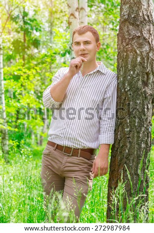 Romantic guy in the park, standing near birch tree with straw in the mouth, carefree weekend, enjoying beauty of spring nature  - stock photo