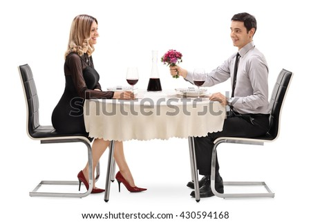 Romantic guy sitting on a date with a blond girl and giving her a flower isolated on white background