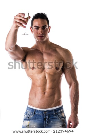 Romantic handsome muscular shirtless young man offering a flute of sparkling champagne to the camera with a smile isolated on white