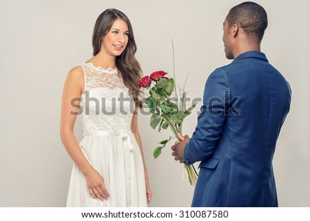 Romantic handsome young African man proposing to his sweetheart as he clutches a bunch of long stemmed red roses in his hand, view over his shoulder from behind, while she is smiling at him - stock photo