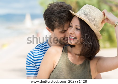 Romantic happy couple at the beach smiling and laughing as the man nuzzles his girlfriends neck