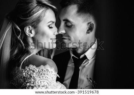 Romantic happy couple, bride & groom kissing near window closeup b&w - stock photo