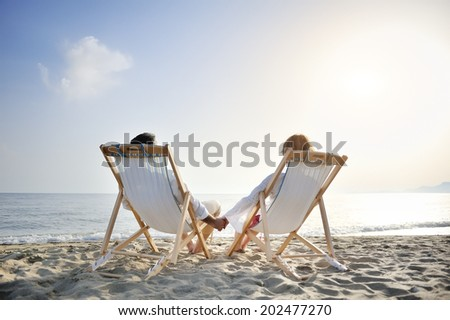 romantic happy couple on deckchair relaxing and enjoying sunset on the beach - stock photo
