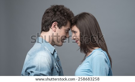 Romantic happy couple touching foreheads and staring at each other's eyes - stock photo
