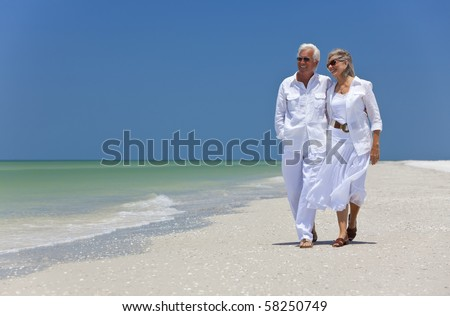 Romantic happy senior man and woman couple walking on a deserted tropical beach with bright clear blue sky - stock photo
