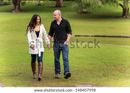 romantic happy young couple holding hands walking in a beautiful park  - stock photo