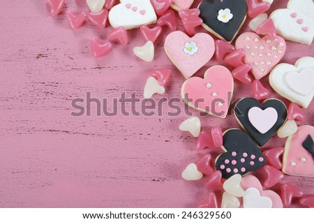 Romantic heart shape pink, white and black cookies and candy background on vintage shabby chic pink wood table with copy space, overhead. - stock photo