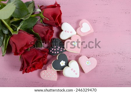 Romantic heart shape pink, white and black cookies with red roses and copy space on vintage shabby chic pink wood table for Valentine or wedding day, overhead. - stock photo
