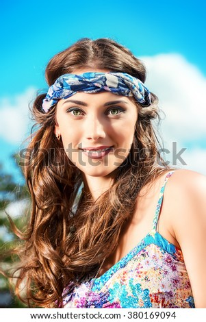 Romantic hippie girl standing outdoor in the summer day over blue sky background. Hippie style. Child of nature.  - stock photo
