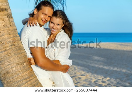 Romantic Honeymoon couple hugging on an exotic beach smiling and looking at camera