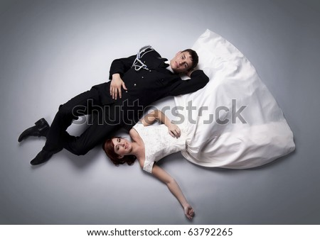 Romantic image of just married couple laying on the floor together and looking at each other