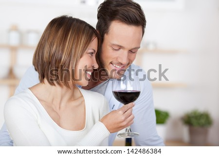 Romantic in love couple with a glass of red wine in the kitchen - stock photo