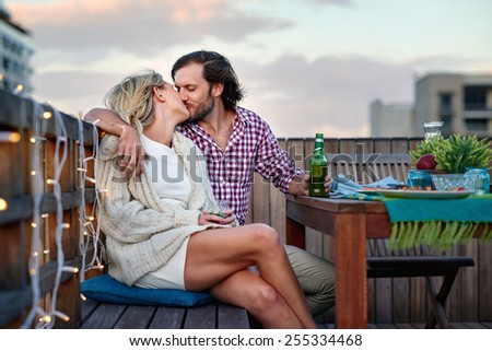romantic kiss couple at rooftop barbecue evening - stock photo