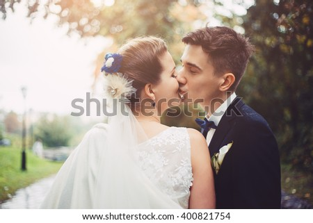 Romantic kiss of newlyweds. Groom and bride are kissing. Bride is smiling, she happy.  They are walking in park at their wedding day. Newlyweds in love. They became husband and wife this day.  - stock photo