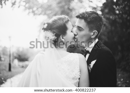 Romantic kiss of newlyweds. Groom and bride are kissing. Bride is smiling, she happy.  They are walking in park at their wedding day. Newlyweds in love. They became husband and wife this day.