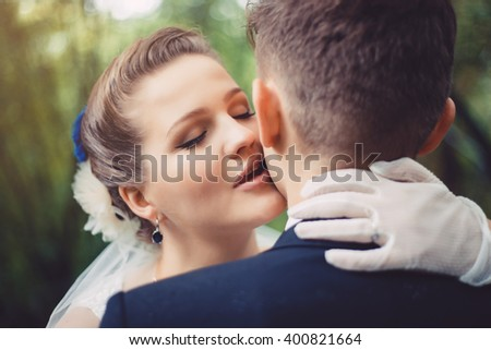 Romantic kiss of newlyweds. The bride is kissing the groom. They are walking in park at their wedding day. Newlyweds in love. They became husband and wife this day.