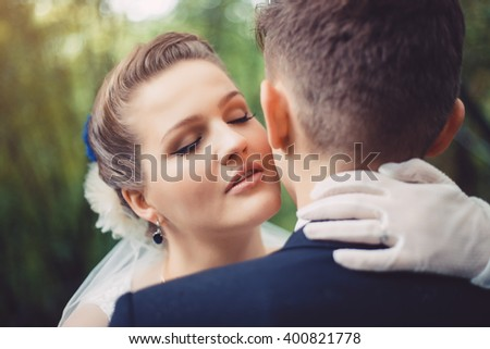 Romantic kiss of newlyweds. The bride is kissing the groom. They are walking in park at their wedding day. Newlyweds in love. They became husband and wife this day.   - stock photo