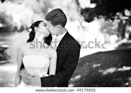 Romantic kiss the bride and groom at the wedding walk - stock photo