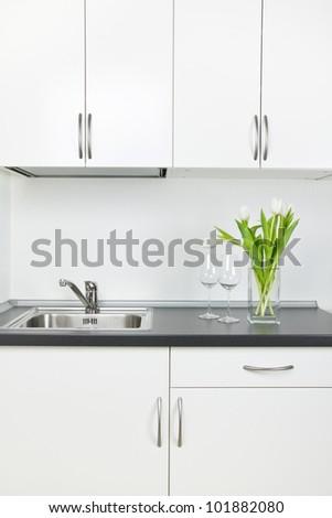 Romantic kitchen interior, empty wineglasses and tulips - stock photo