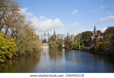 Romantic lake Minnewater in Autumn with its famous house with towers and Church Of Our Lady in Bruges, Belgium. - stock photo