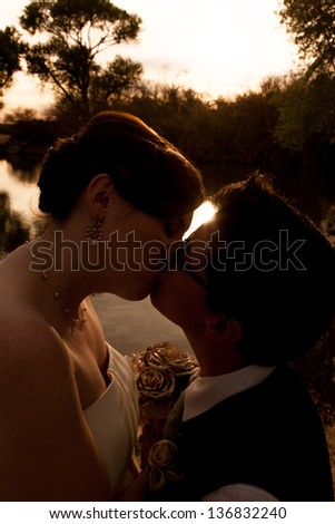 Romantic lesbian couple kissing near sunset outdoors - stock photo