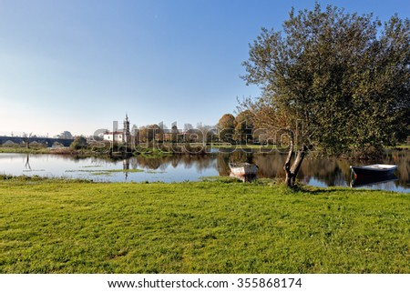 Romantic Lima River near the old granite bridge of medieval city of Ponte de Lima, north of Portugal - stock photo