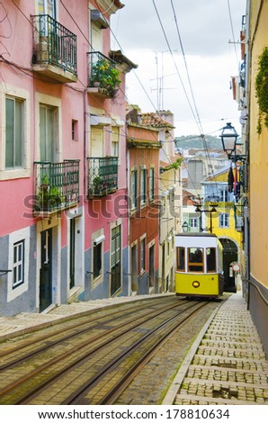 Romantic Lisbon street with the typical yellow tram - stock photo
