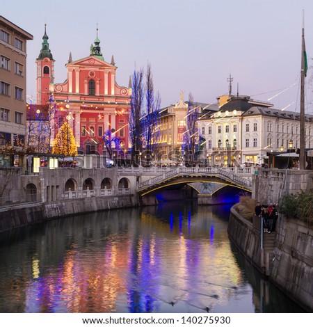 Romantic Ljubljana's city center  decorated for Christmas time. River Ljubljanica, Triple Bridge (Tromostovje) and  Preseren's square; Ljubljana, Slovenia, Europe. - stock photo