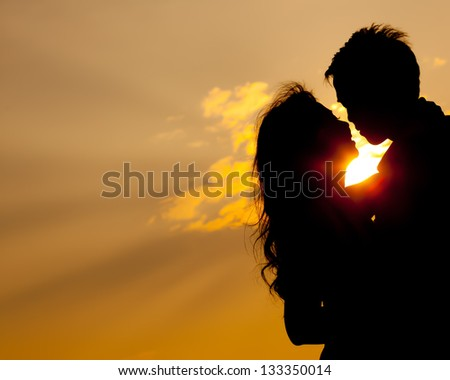 Romantic lovers hugging at twlilight with sunset in background - stock photo