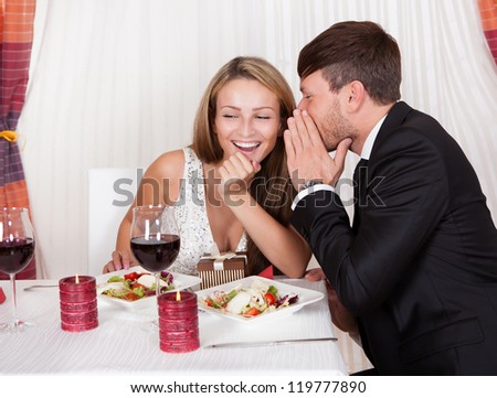Romantic lovers sitting at an elegant restaurant table enjoying a meal and sharing secrets whispering to each other - stock photo