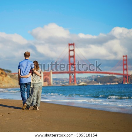 Romantic loving couple having a date on Baker beach in San Francisco, California, USA. Golden gate bridge in the background