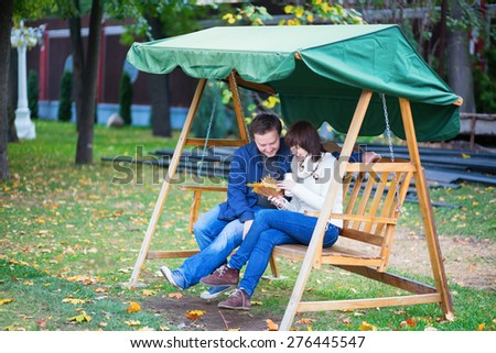 Romantic loving couple having fun together on the swing