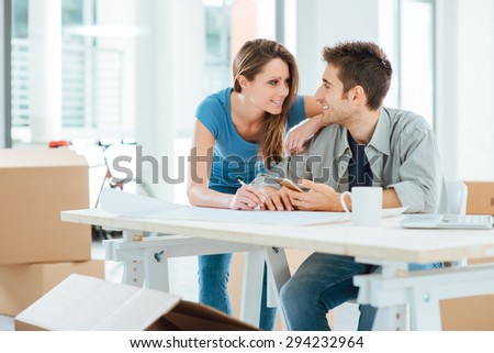Romantic loving couple planning and designing their new house, they are staring at each other's eyes - stock photo