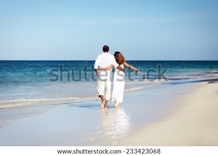 Romantic loving couple walking on the beach. Caribbean vacation.       - stock photo