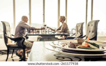 romantic lunch at the restaurant. couple making toast with red wine.straight focus on the  plate with food on the front table - stock photo