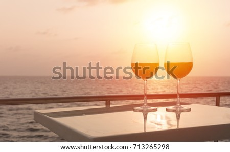 Romantic luxury evening on cruise yacht with winery setting. Glasses and bottle with red wine and tropical sunset with sea background, nobody.